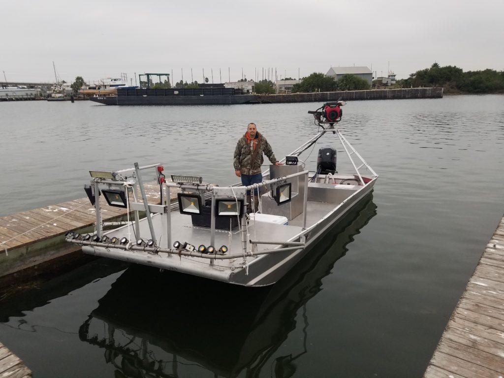 A fishing guide in Aransas Pass standing on a Flounder gigging boat
