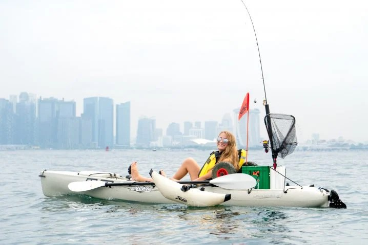 A blond woman in sunglasses sitting in a white fishing kayak on the sea with a cityscape behind her in the distance