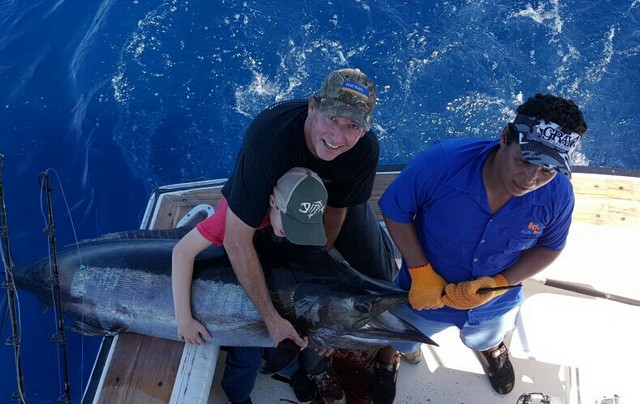 A man Marlin fishing with his son. The pair have caught a large Black Marlin and a deckhand is helping them pose with it before it is released