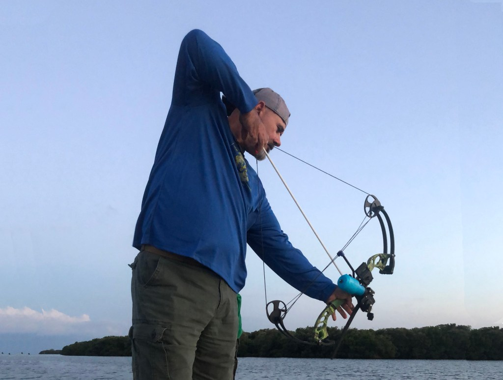 Fisherman aiming bowfishing gear at water