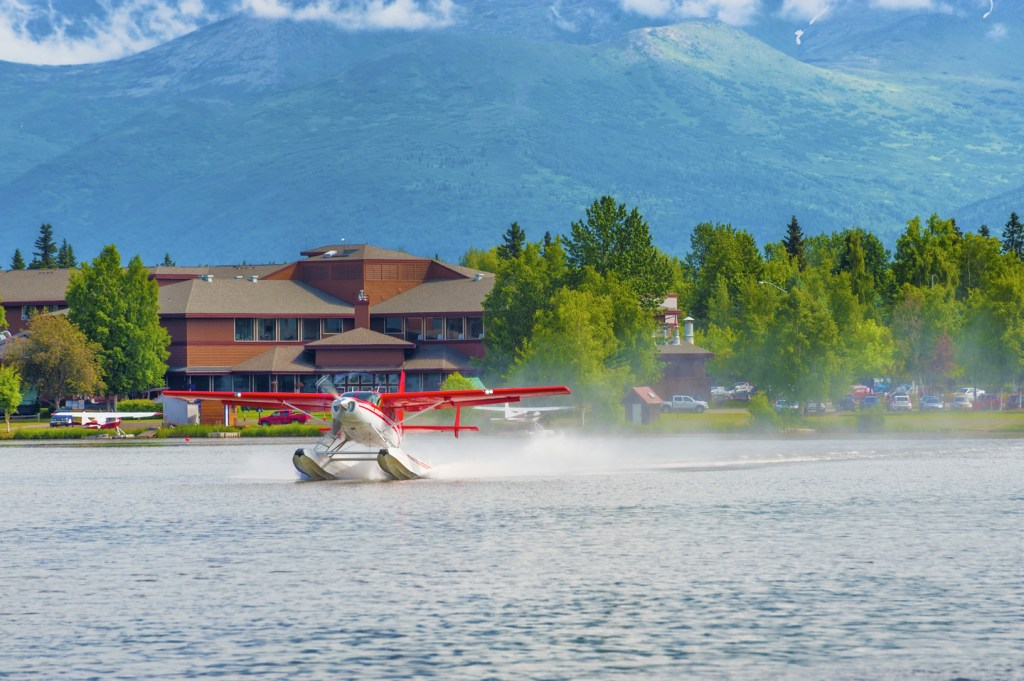a red and white seaplane landing on a lake near Anchorage, Alaska