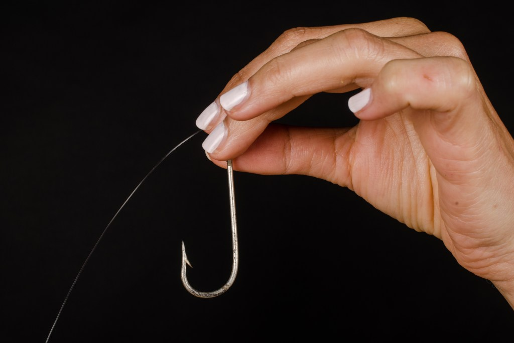 A woman's hand with white nail polish holding an Aberdeen fishing hook against a black background