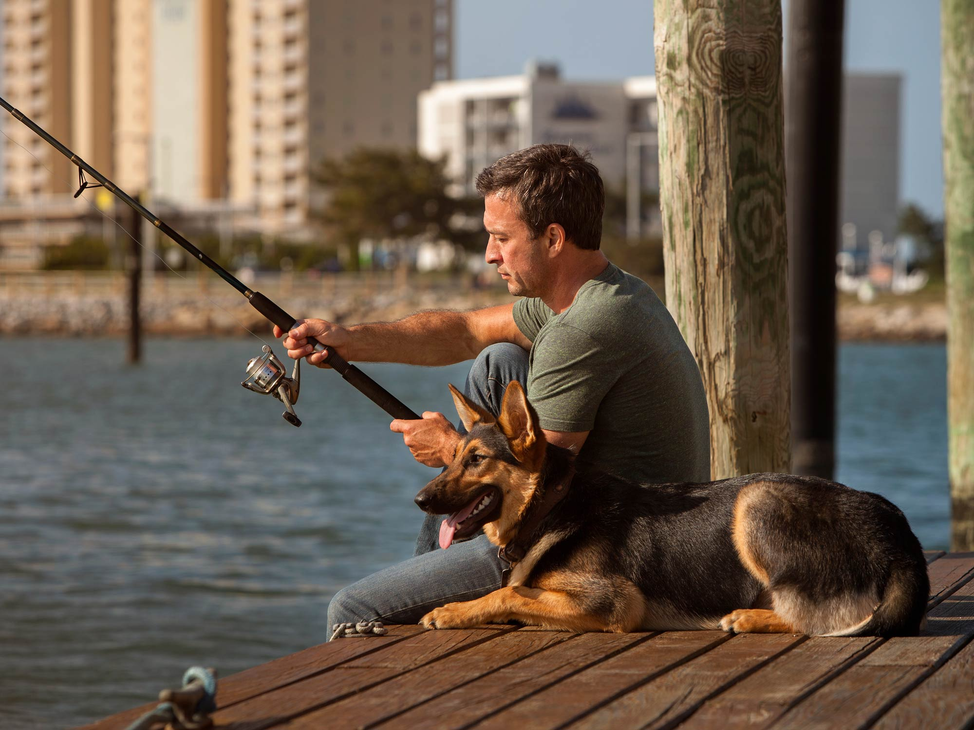 Angler fishing from a dock with his dog next to him
