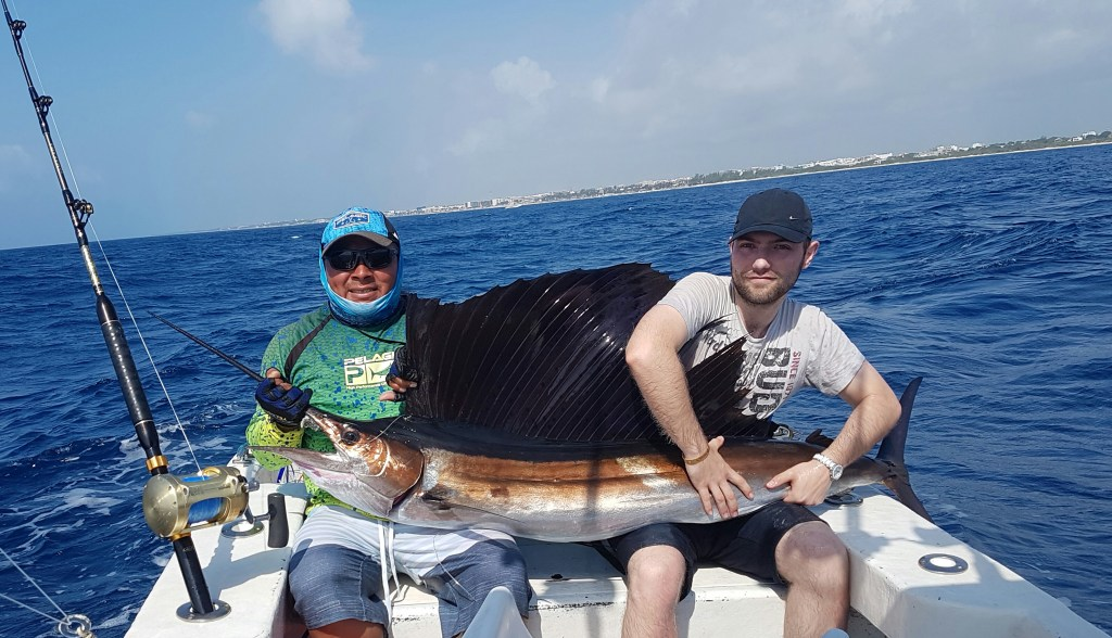 anglers holding a Sailfish on a fishing boat