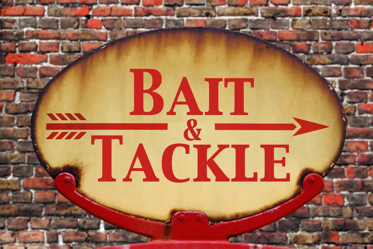A vintage red and yellow bait and tackle sign against a brick wall