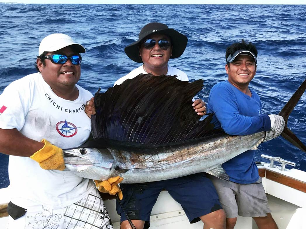 Three men smiling as they hold up a big Sailfish on board a sportfishing vessel