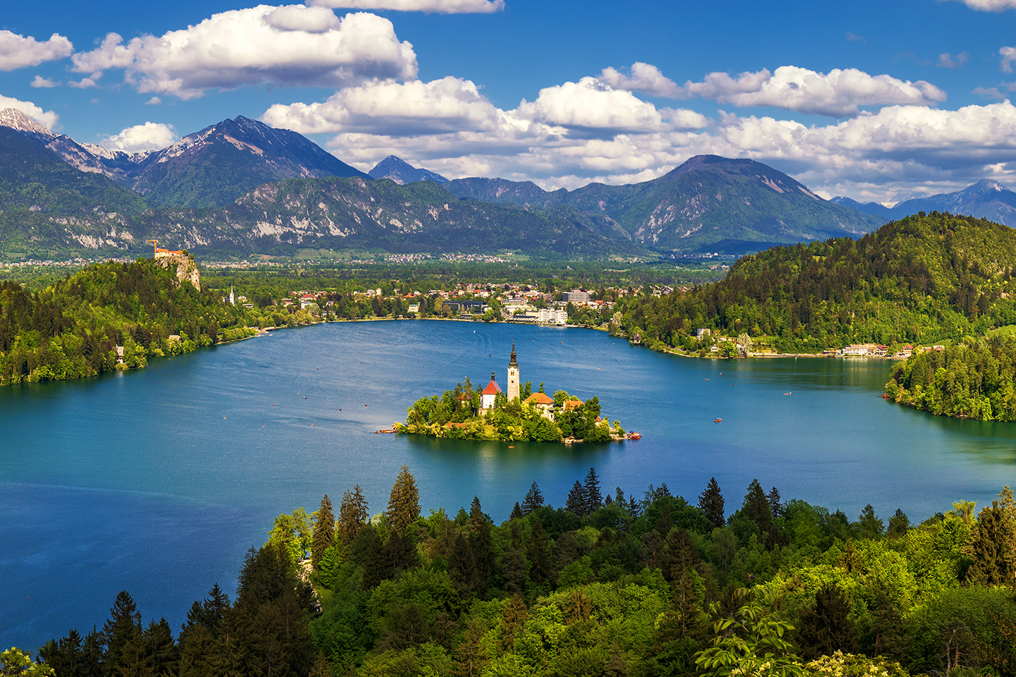 An aerial view of Lake Bled in Slovenia, with a church on an island in the middle and mountains in the distance.