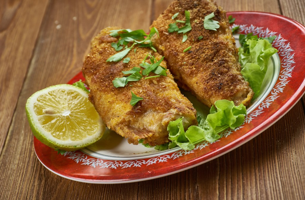Two whole fried Bluegill fish on a plate, with half a lime and some herbs and lettuce leaves scattered around it.
