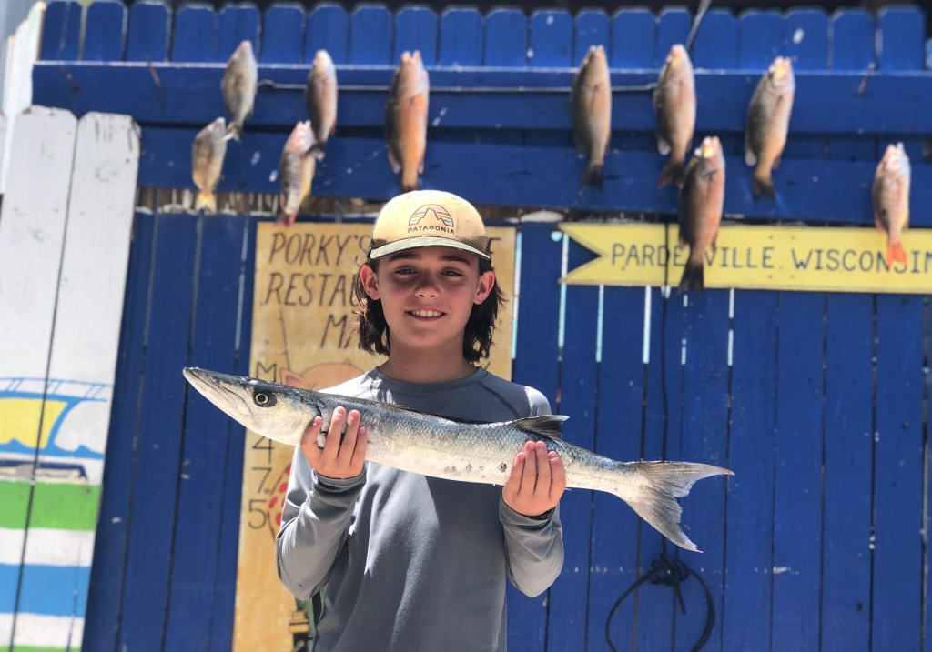 Young boy holding a barracuda in front of a fish board