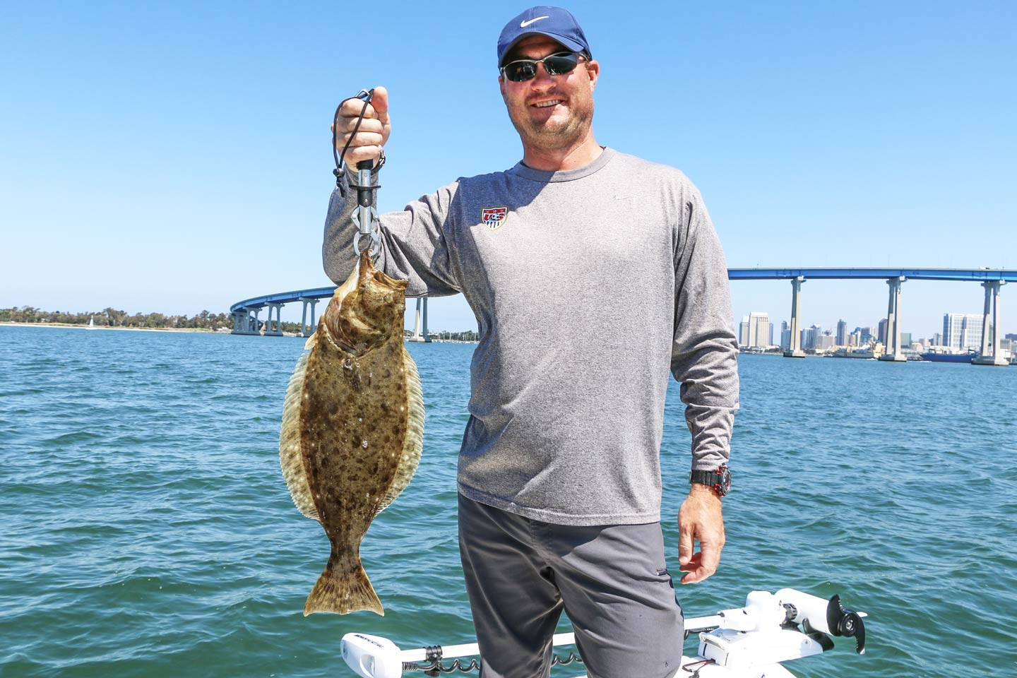 A male angler holding a smaller California Halibut aboard a charter fishing vessel.