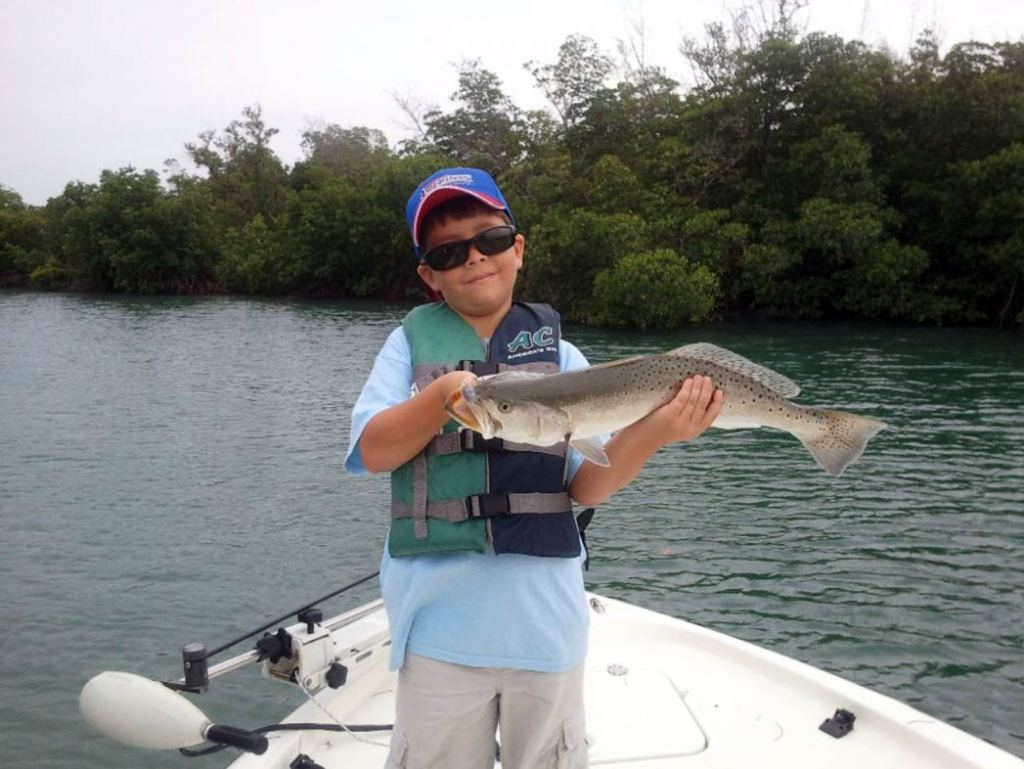 A boy proudly displays his Speckled Trout on board a boat on the Indian River
