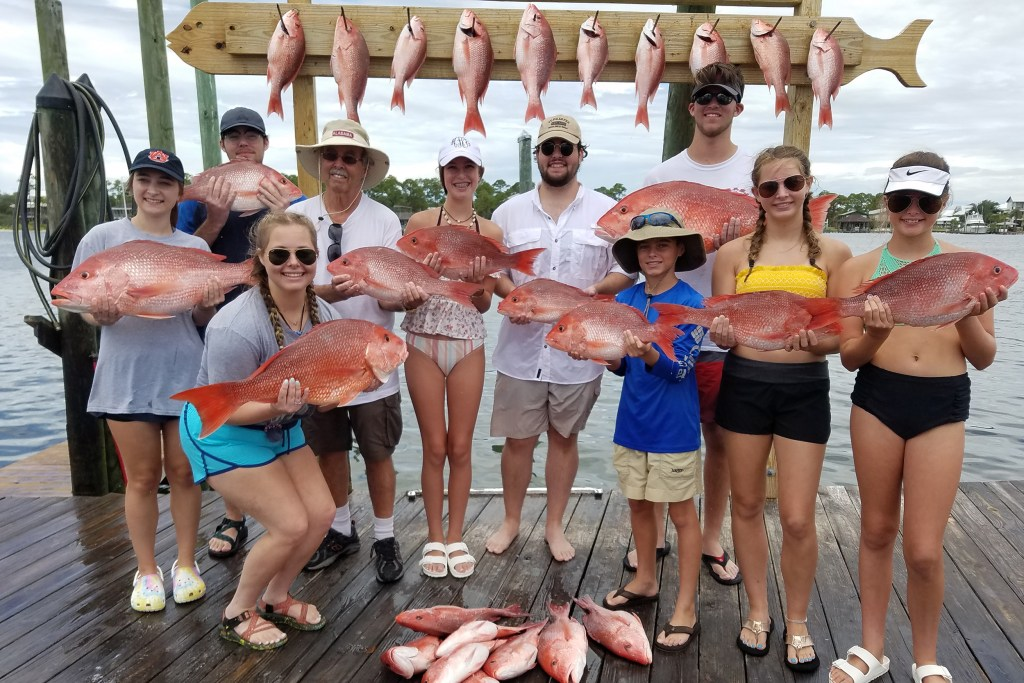 A large family group holding red snapper caught on a fishing charter
