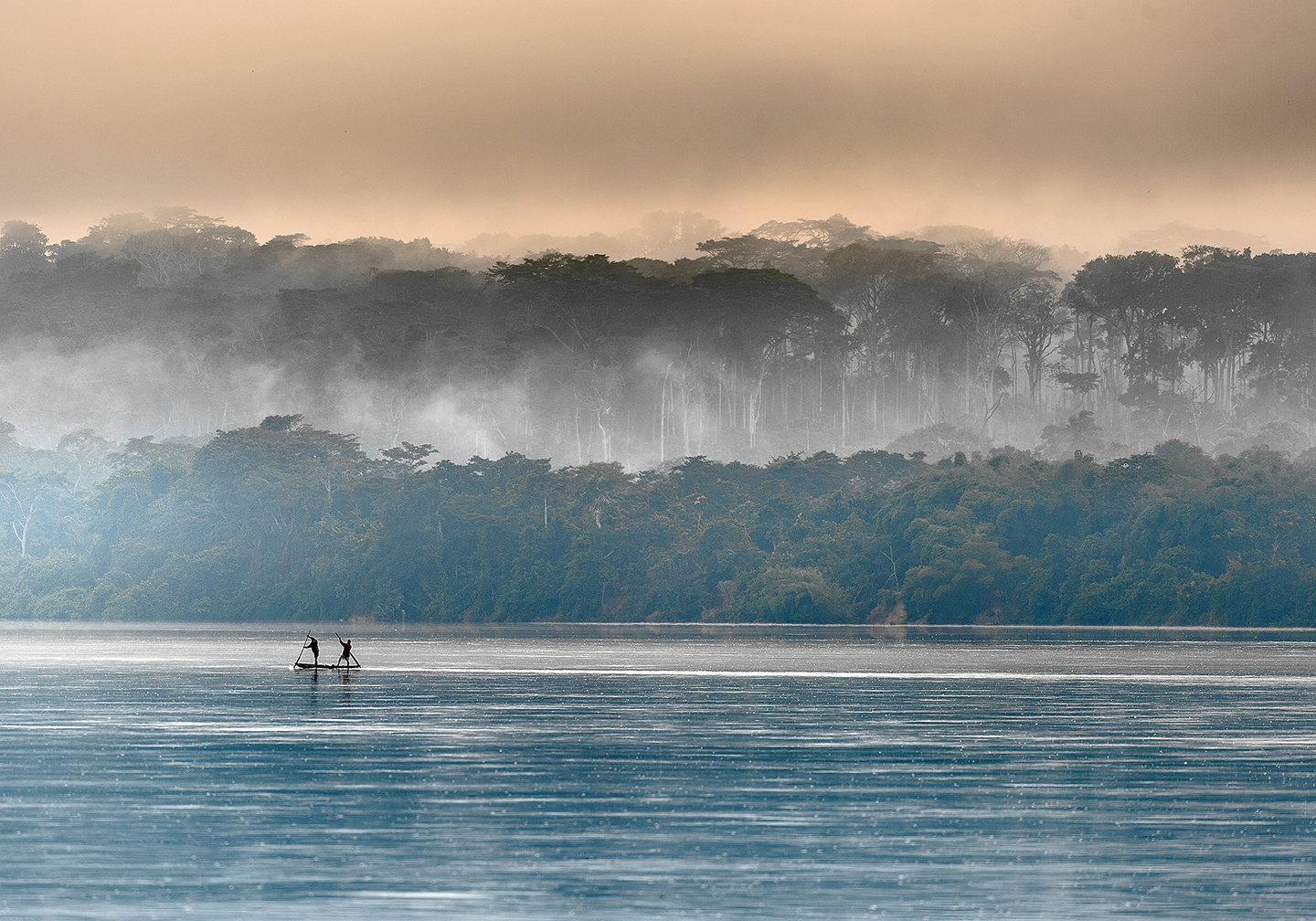 Two fishermen in the distance on the Congo River, with trees and sky behind them