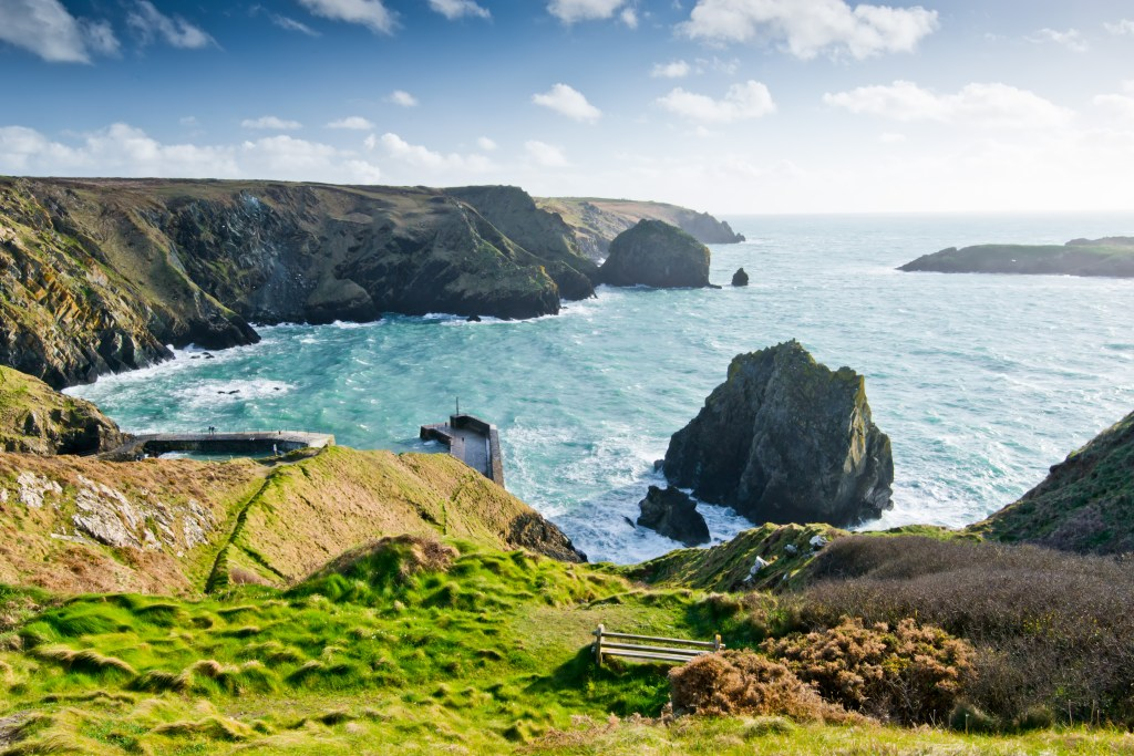 A sunny day on the Cornish coast, with rocky cliffs and green-blue sea
