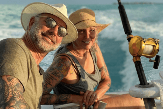 A happy couple sitting on a moving boat while holding hands, with a fishing rod right next to them.