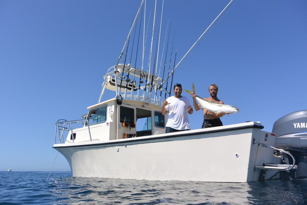 Two men on a small sportfishing boat. One of them is holding a Yellowtail Amberjack