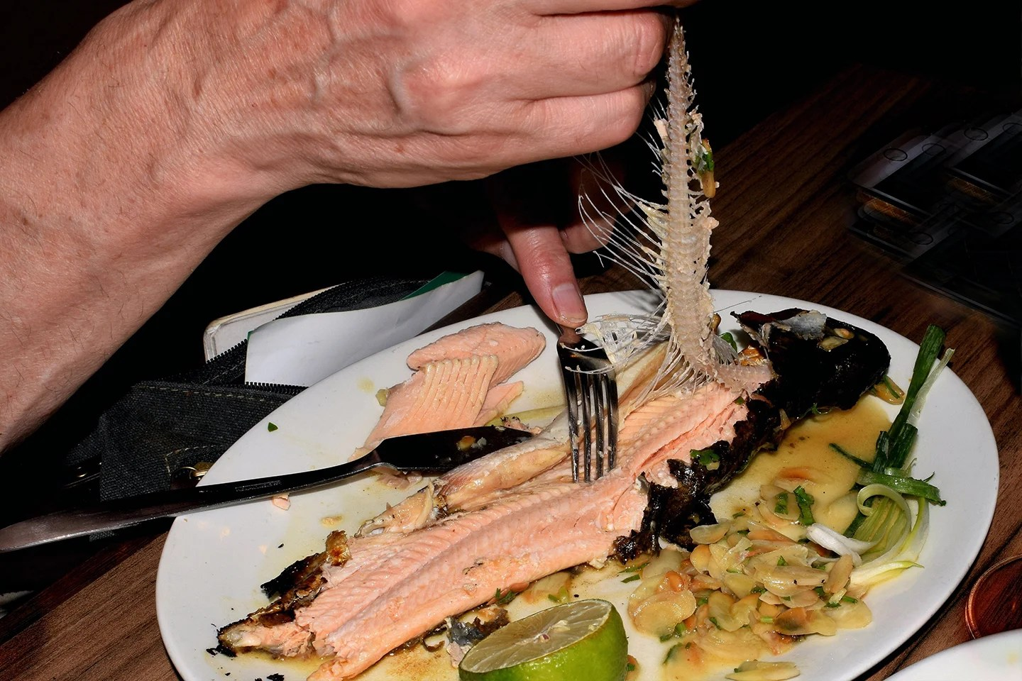 A man deboning a Trout by pulling the spine off the bottom half of the fish