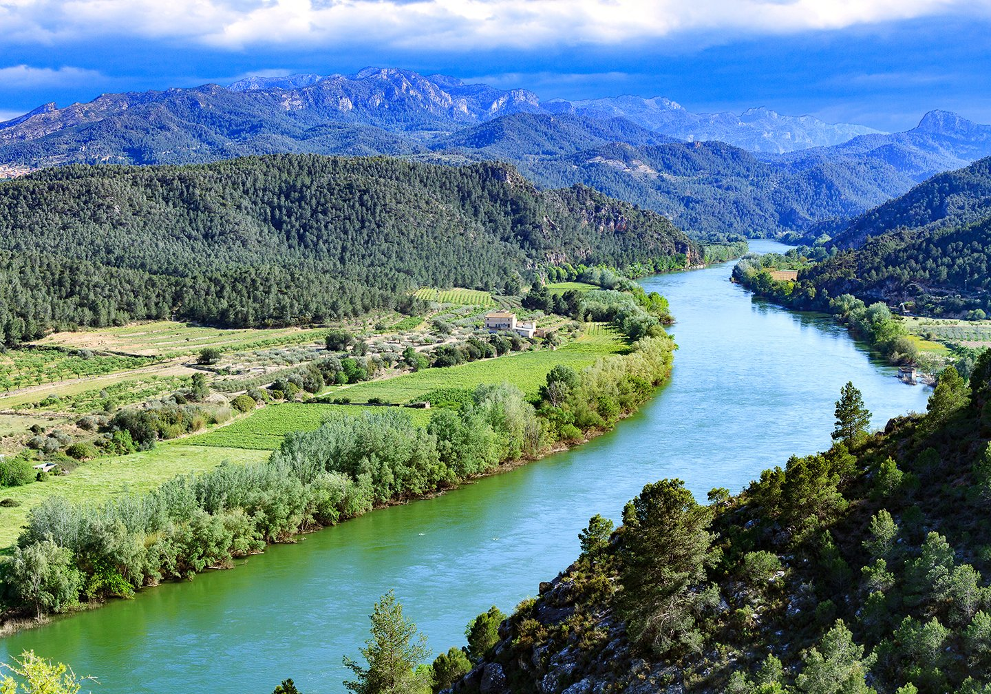 The Ebro River in Spain, with green fields on either side and blue mountains in the distance