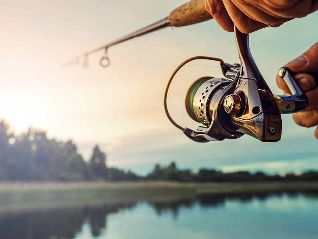 A fishing reel held by an angler with a lake in the distance