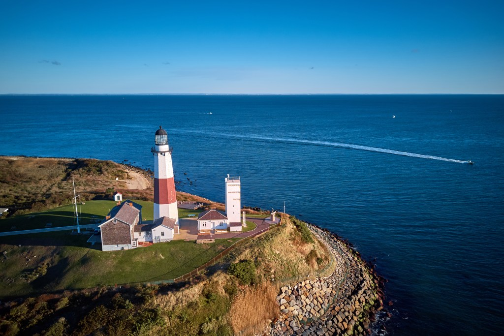 An aerial view of Montauk Lighthouse, with a fishing boat in the sea in the distance