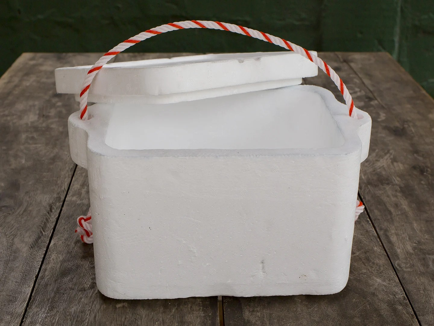 A styrofoam box with a red and white handle on a wooden table