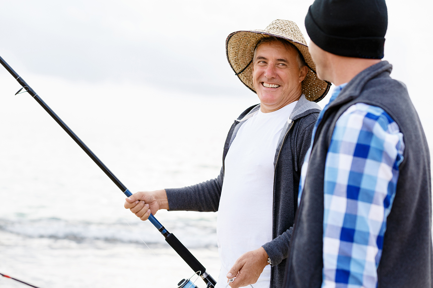 Two happy fishermen, one with a rod in his hand