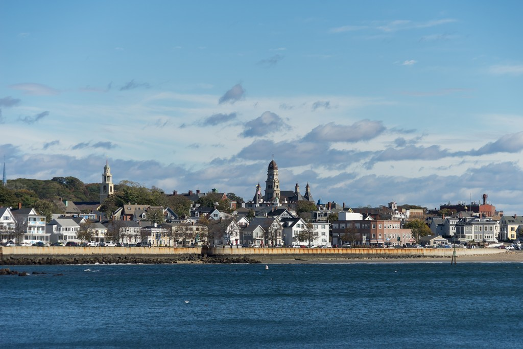 A view from the ocean of Gloucester, Massachusetts, with old church spires poking above the houses