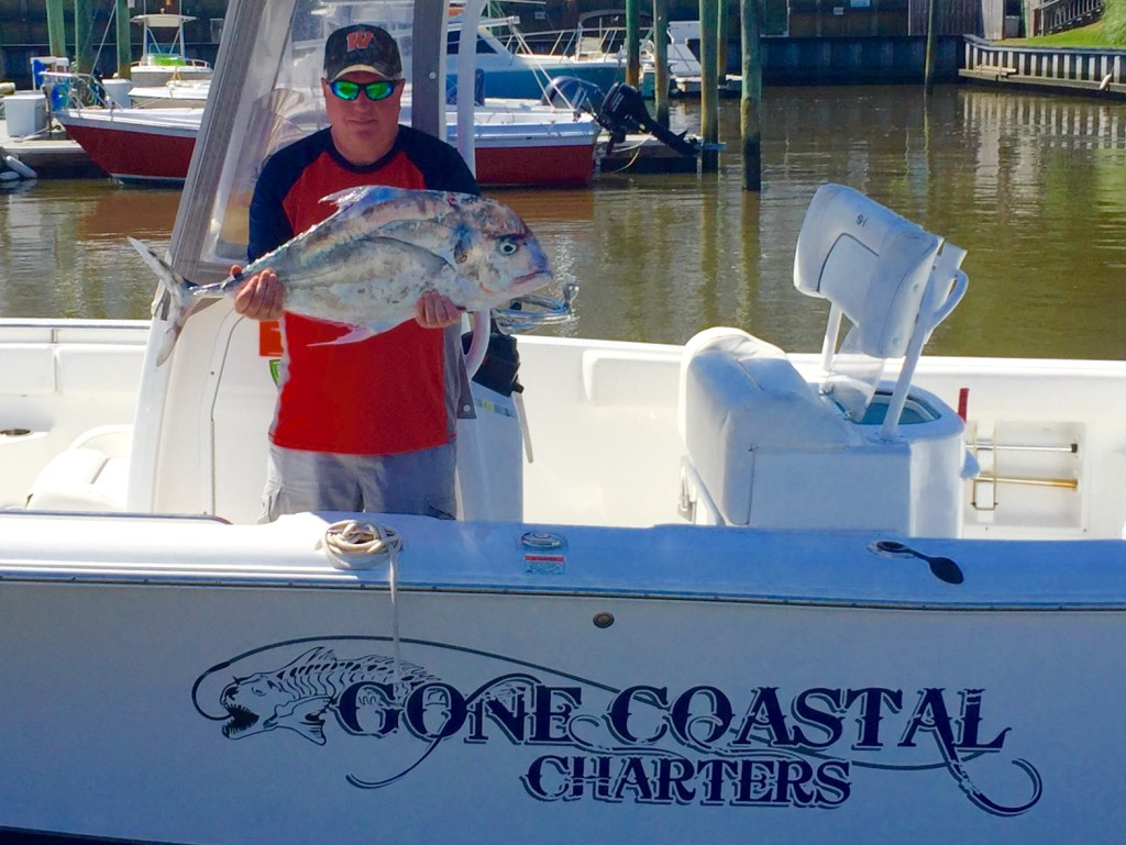 Man holding fish aboard a boat with a Gone Coastal Charters decal