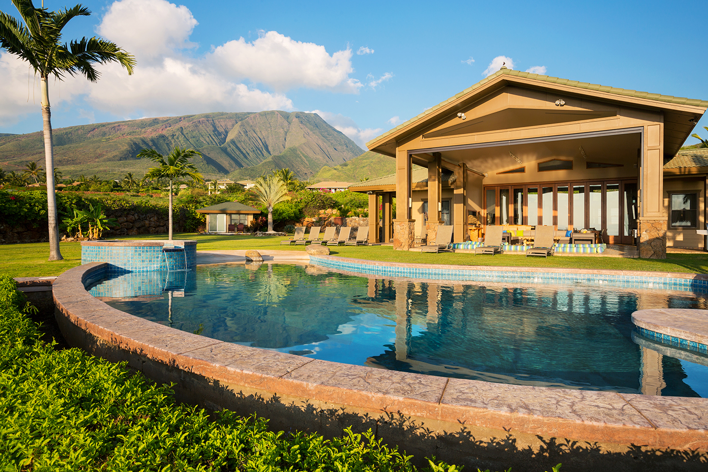 A luxurious tropical resort with a swimming pool, lawn, palm trees, and a mountain in the distance.