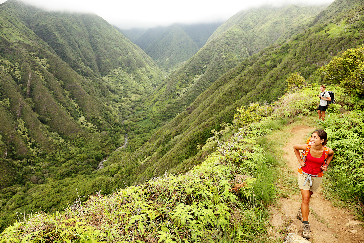 Two hikers walking along a mountain trail in Hawaii: a woman in a red tank top and beige shorts, and a man in a blue shirt and black shorts.