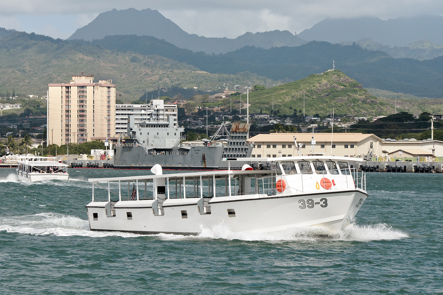 A white ferry boat heading out from a harbor on Hawaii, with another ferry heading into port behind it and high, dark mountains in the distance.