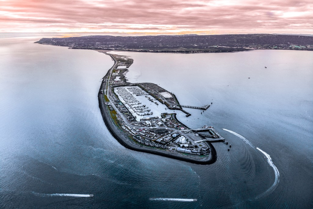 An aerial view of Homer Spit, with boats cruising past into Kachemak Bay
