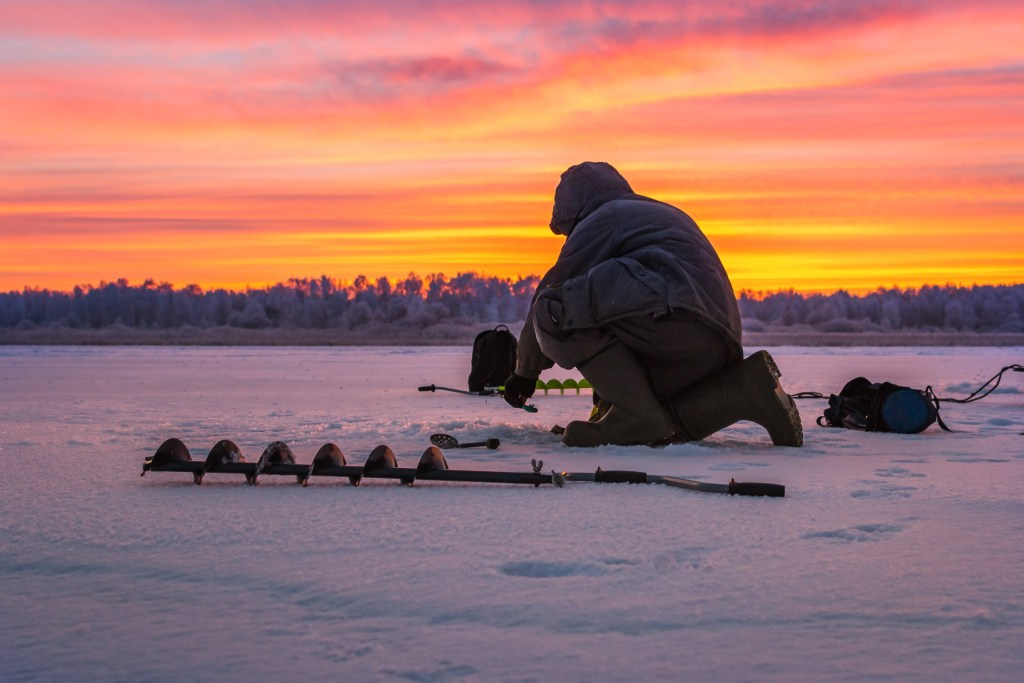 A dedicated ice fisherman drilling a hole at sunrise