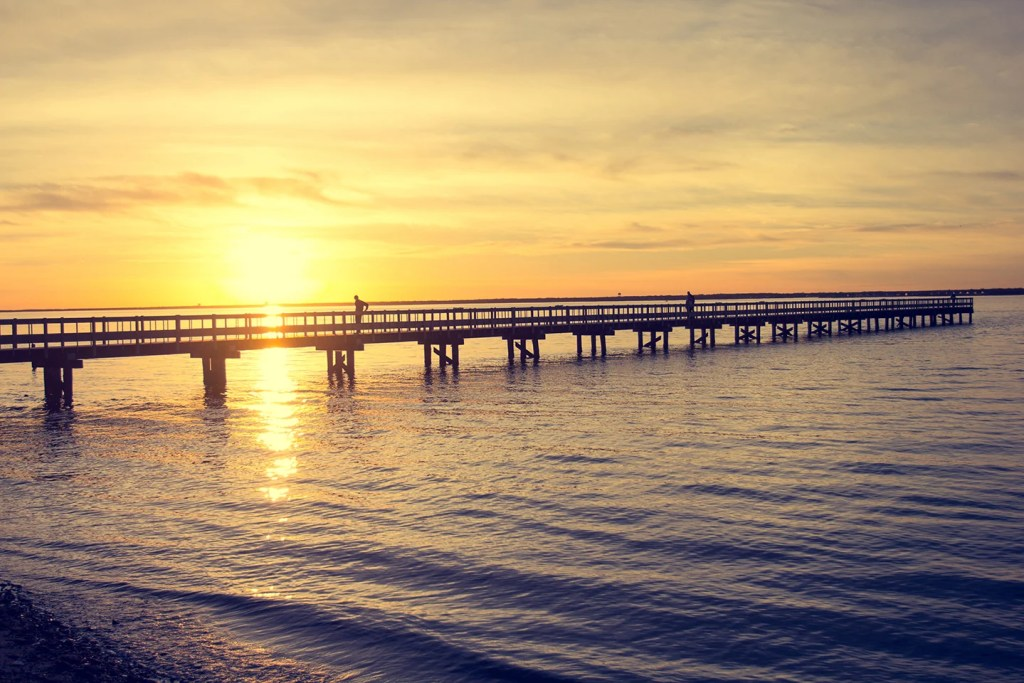 A wooden pier stretching into the water, with the sun setting behind it.