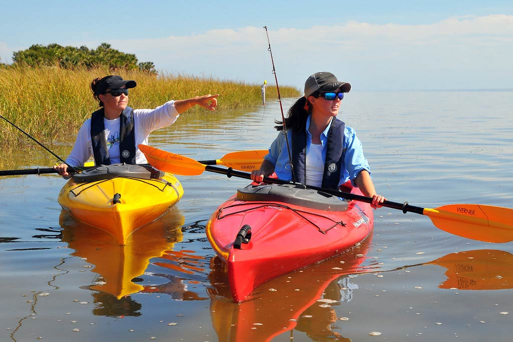 Two women kayaking through the flats with fishing rods, while one points to their left