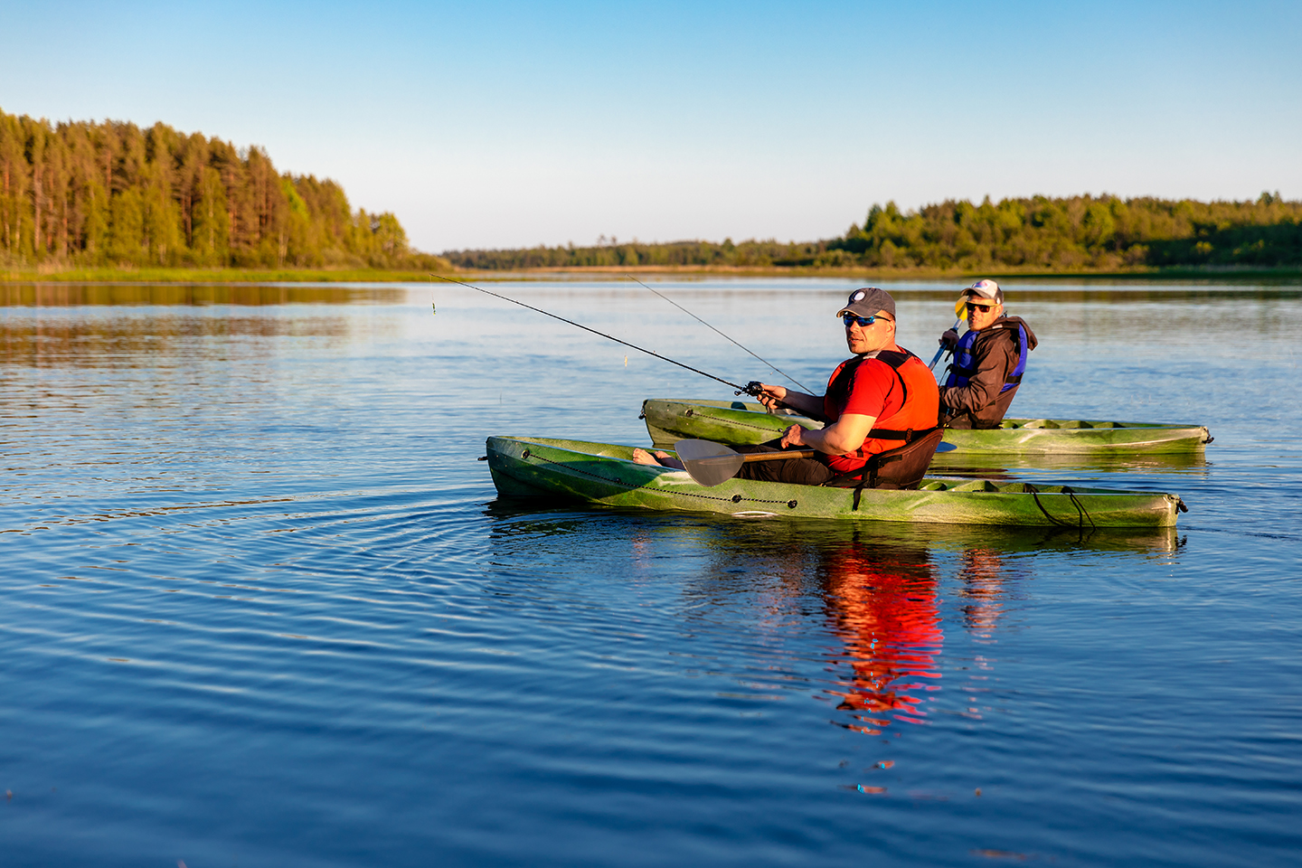 Two men kayak fishing together on a lake as part of a fishing therapy session