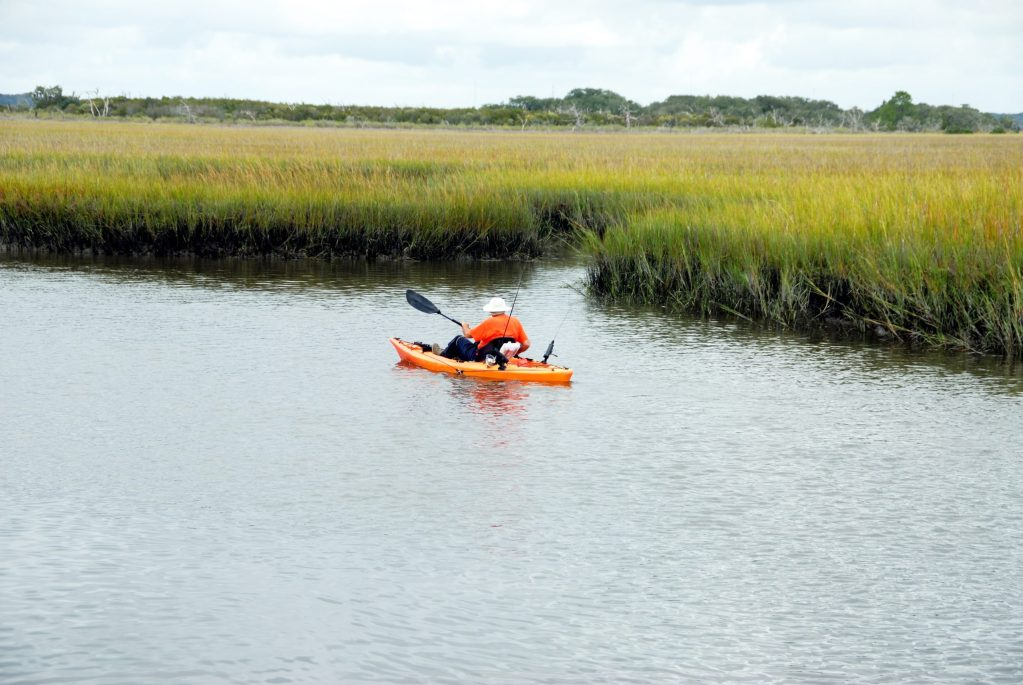 A man fishes the lake from an orange kayak
