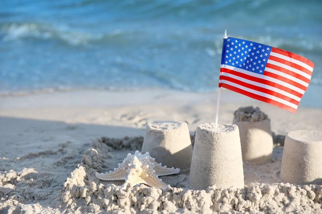 An American flag stuck in a collection of sand castles on a white beach, with blue sea in the distance