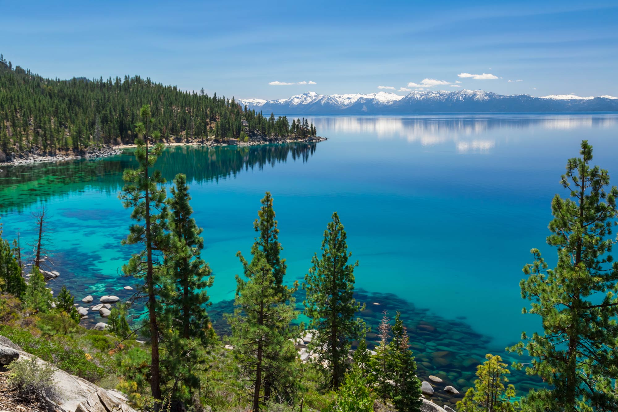 An aerial view of Lake Tahoe with mountains and blue skies in the background
