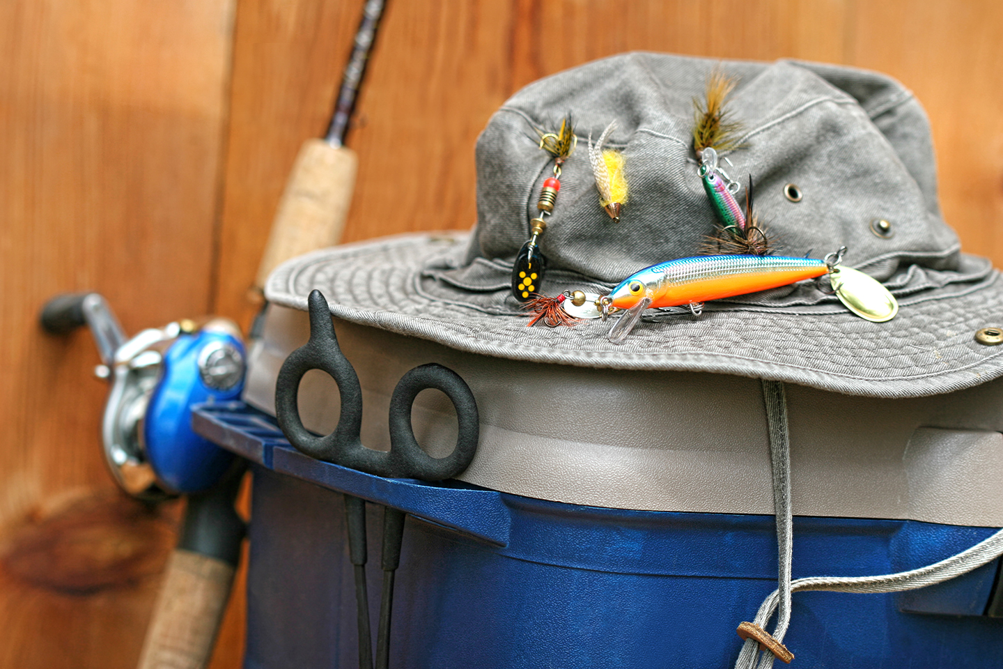 A lucky fishing hat, one of the most common common fishing superstitions, rested on a cooler with a fishing rod behind