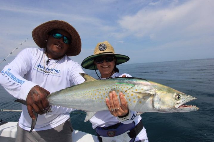 Man and woman holding a Cero Mackerel which has been tagged