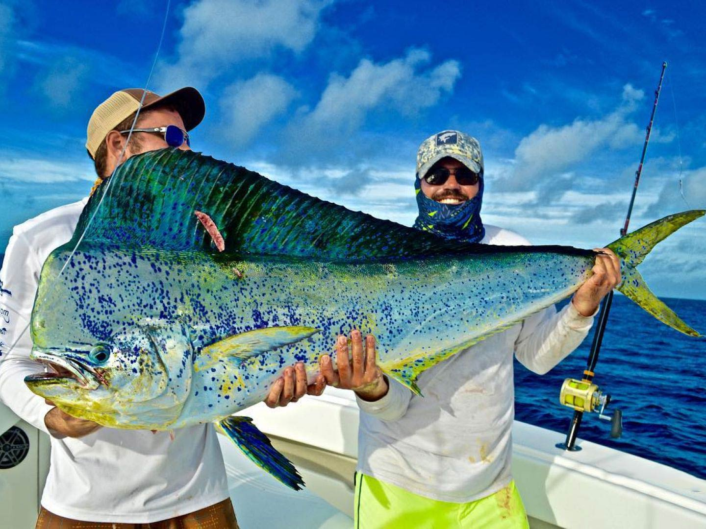 Two men on an offshore vessel smile and hold a large Mahi Mahi