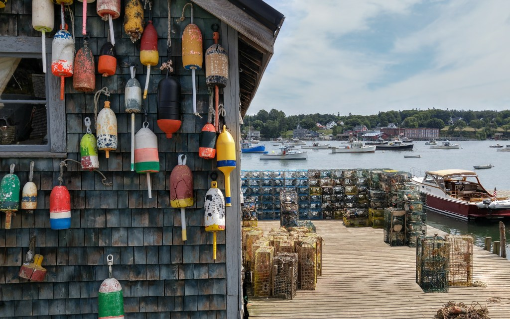 A traditional dock in a fishing village in Maine, with lobster buoys on the wall of a shack in the foreground and fishing boats in the water in the distance