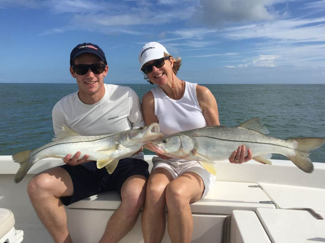 A man and a woman each hold a Snook on board a flats vessel, with the water in the background