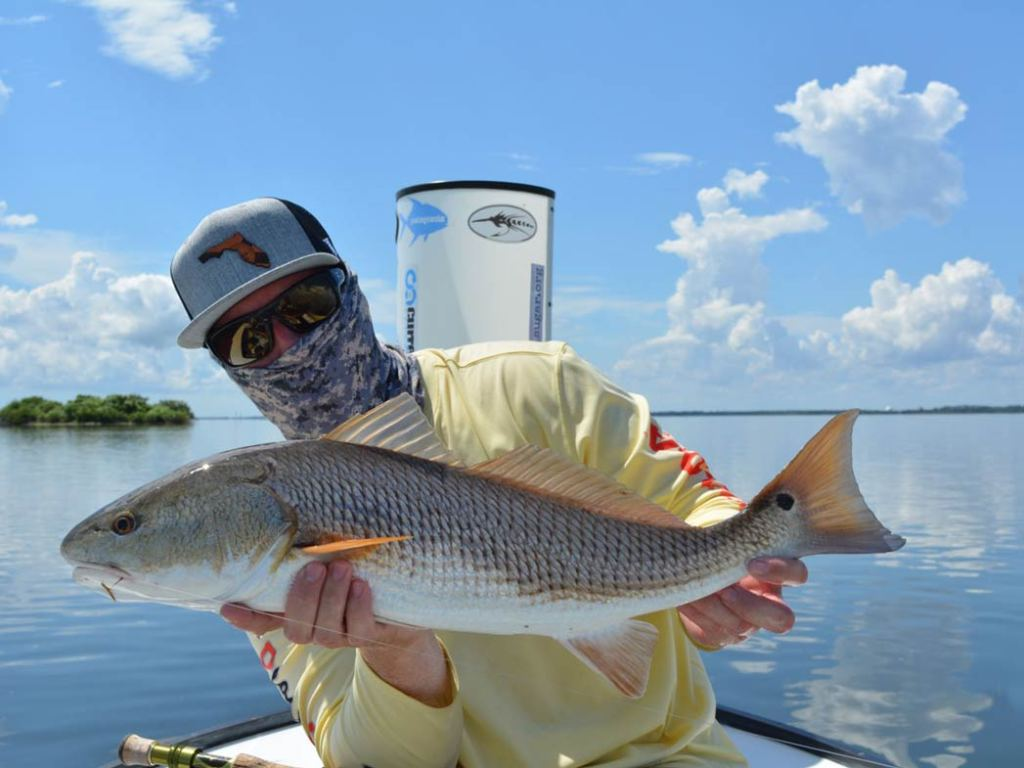 A man poses on a flats boat holding a big Redfish on the Indian River
