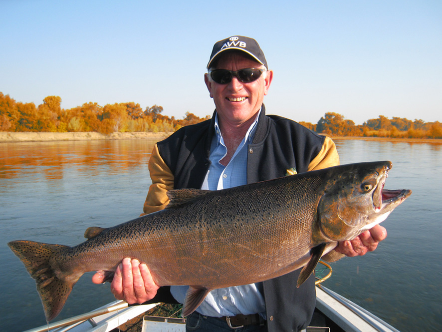 A man holding a big fish on a boat on the Trinity River.