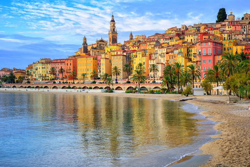 A view from the beach of the colorful fishing town of Menton, France. Yellow and red houses sit on a low hill by the sea, with palm trees lining the waterfront and church spires poking out up into the sky. The buildings are reflected in the calm, shallow sea in the middle of the photo.