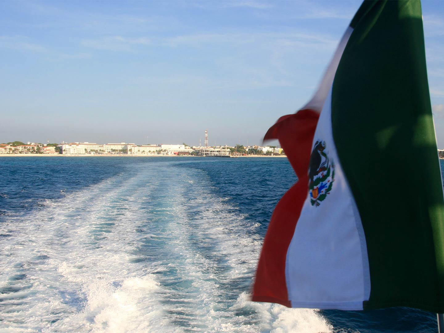 A Mexican flag flutters in the wind looking towards the coastline as a boat sails off into the sea