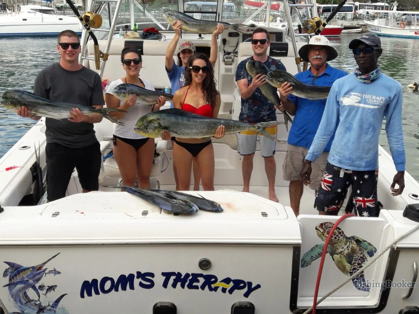 a group of smiling anglers holding fish they caught on a fishing trip in Barbados
