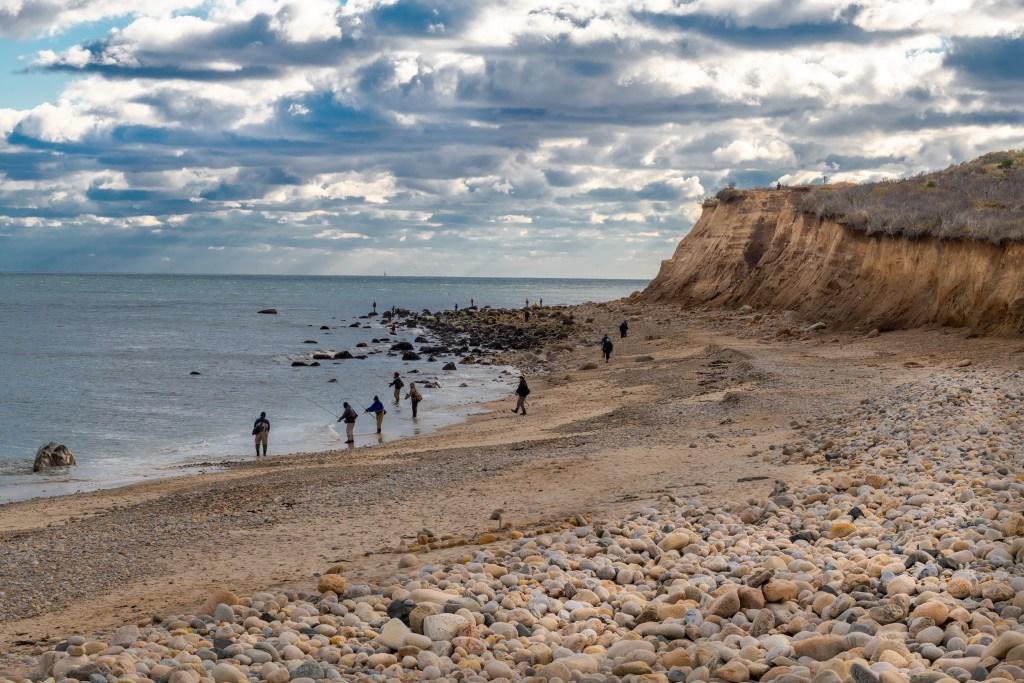 A group of surf fishermen on a rocky beach on Long Island, NY